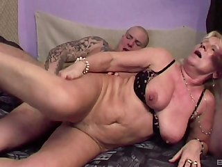 Mature blonde Lizzy is between young dudes during a lewd threesome